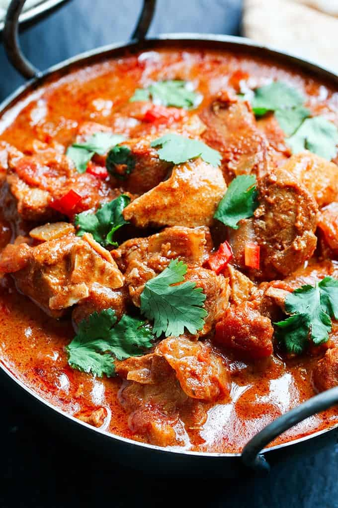 Closeup picture of Slow-Cooked Spicy Chicken Curry in a serving bowl on a dark background