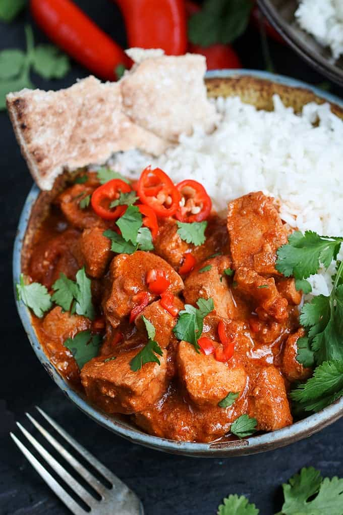 Portrait photo of Slow-Cooked Spicy Chicken Curry with rice and naan in a stone bowl with chillis in the background and a fork in the foreground