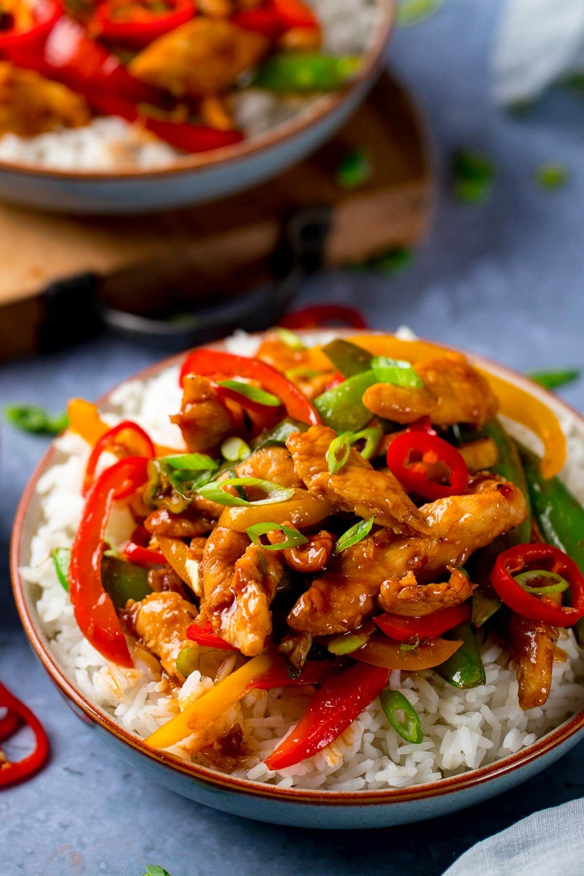 chicken stir fry with rice in a bowl topped with chillies and spring onions
