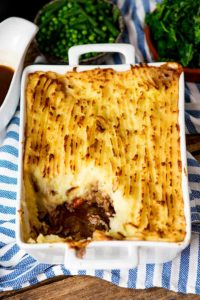Shepherd's pie with creamy mashed potato in a white dish with a scoop taken out.
