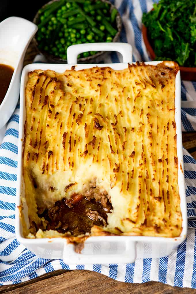 White dish of cottage pie with portion taken out