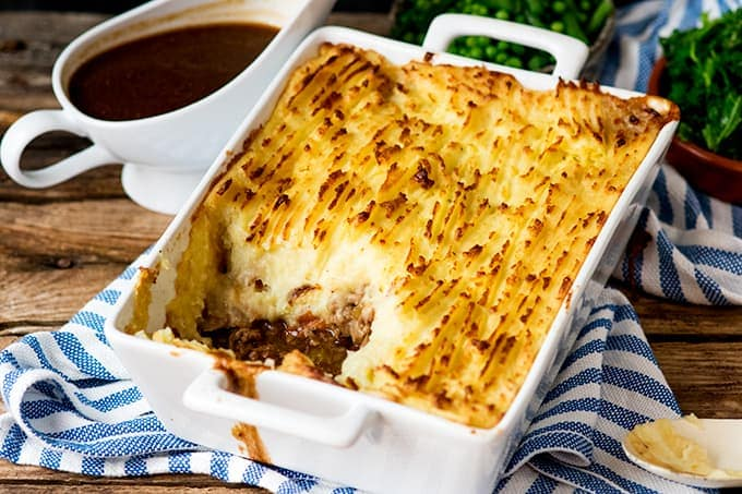 Dish of Shepherd's pie with scoop taken out on a blue and white strip kitchen towel