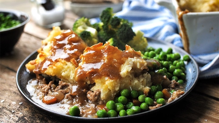 Dark plate with shepherds pie, peas, brocolli and gravy