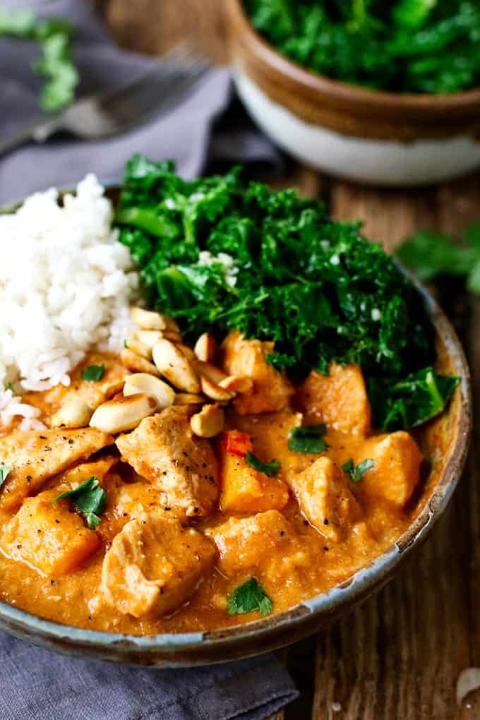 Close up photo of African Stew in a stone bowl with rice and kale