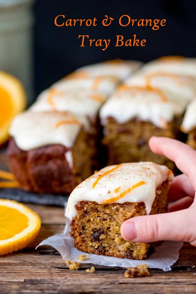 a hand grabbing a piece of carrot tray bake with orange infused raisins and zesty cream cheese frosting