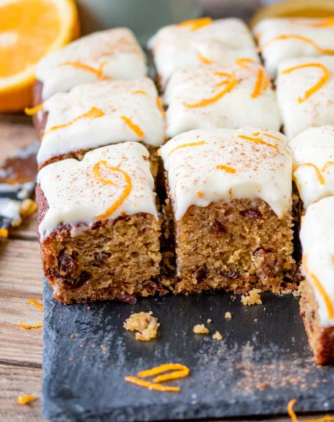 close up of a fluffy moist carrot tray bake with orange infused raisins and zesty cream cheese frosting
