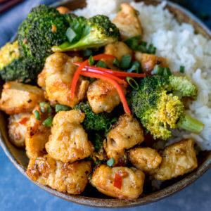 Square image of Asian crispy chicken with broccoli and rice in a stoneware bowl. Blue napkin in background