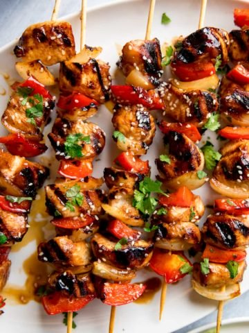 honey garlic chicken skewers on a white plate