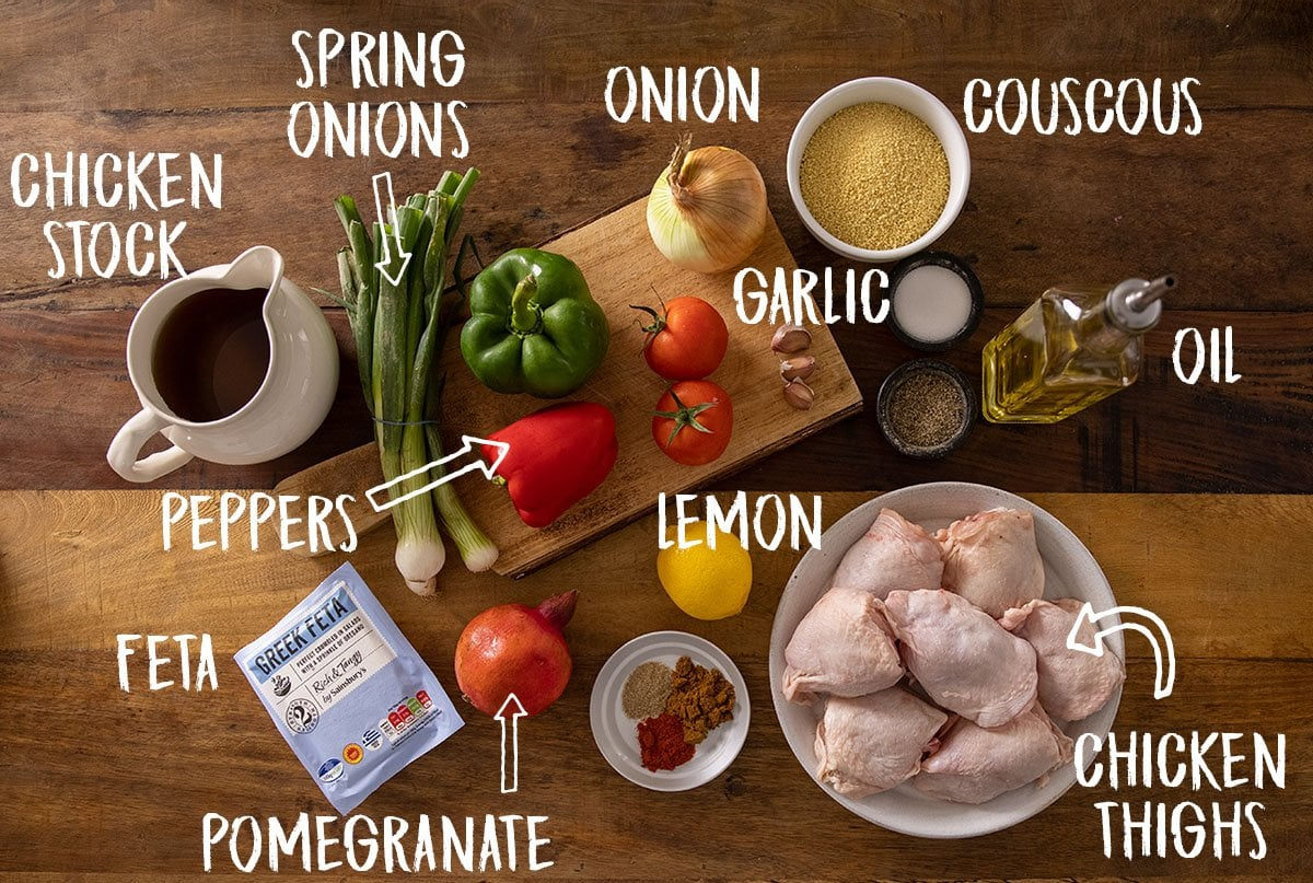 Ingredients for one-pot chicken and couscous on a wooden table