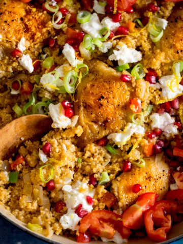 Square image of one-pot chicken and couscous in a blue pan, topped with feta and pomegranate. There is a wooden spoon digging into the couscous.
