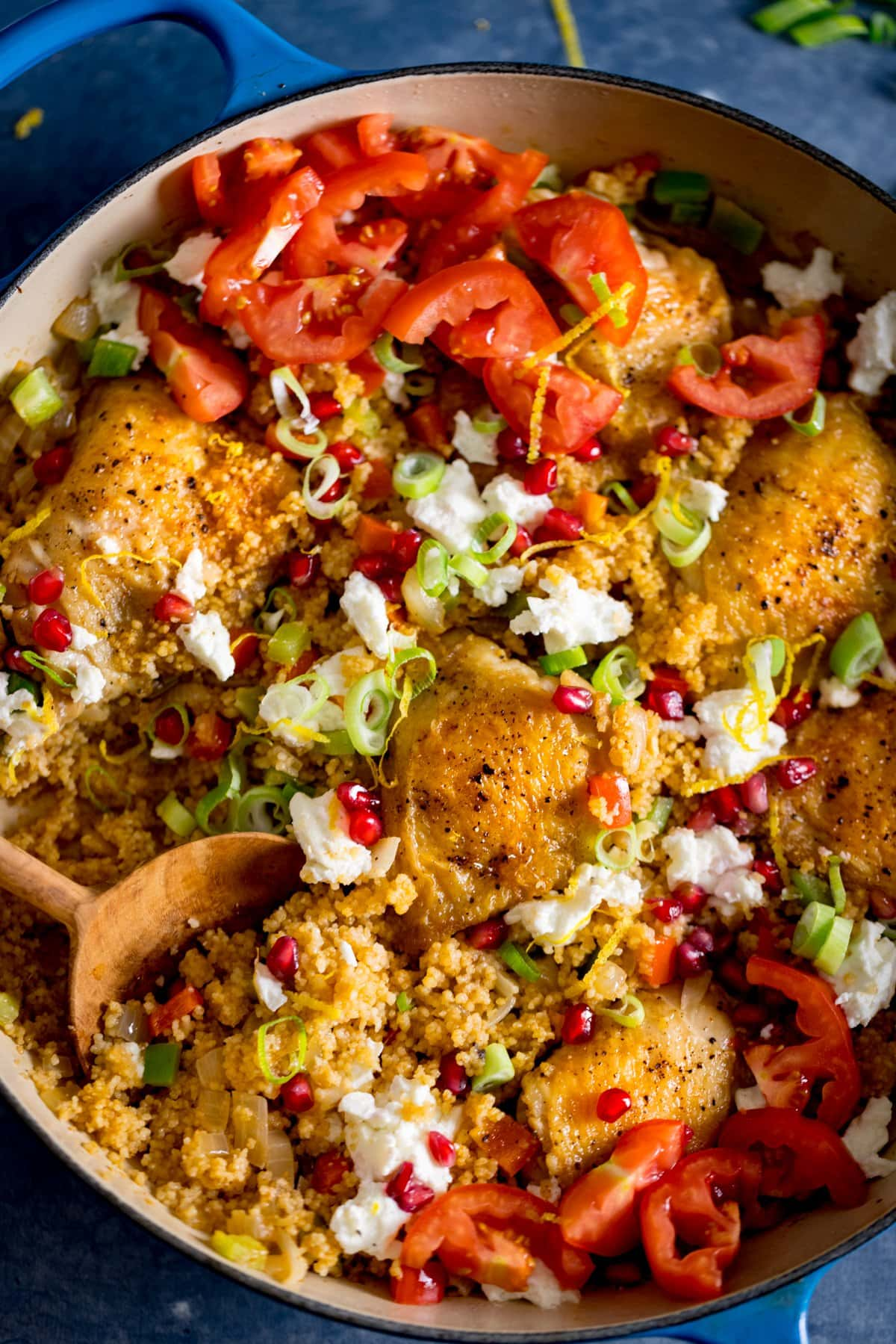 Chicken and couscous one pot in a pan on a blue table. There is a spoonful being taken from the pan. The dish is topped with feta, pomegranate and chopped tomatoes.