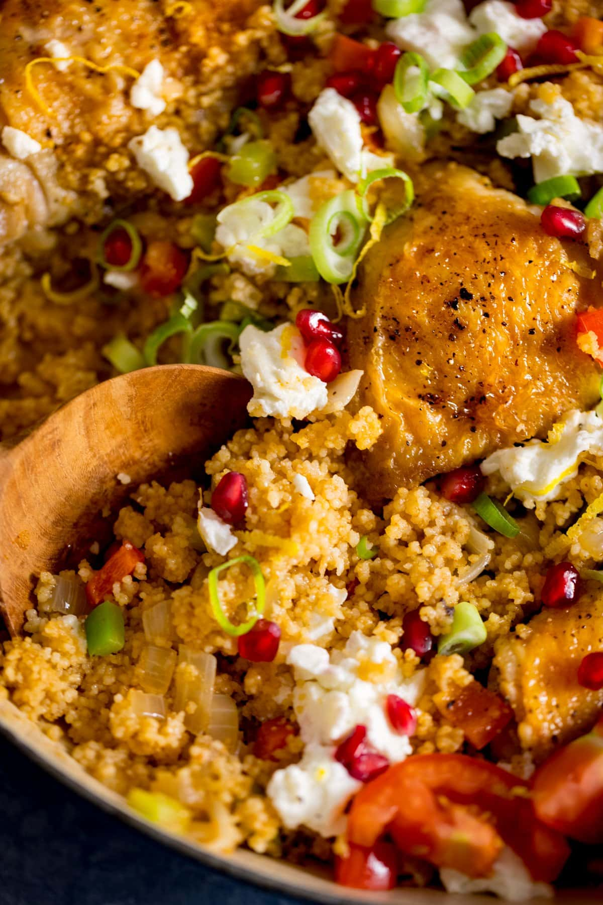 Close up of a wooden spoon taking a spoonful from a pan of chicken and couscous one-pot.