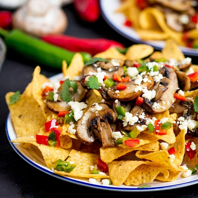 Super quick Nachos topped with garlic mushrooms, chilies and crumbly Lancashire cheese! A great vegetarian appetizer or party dish!