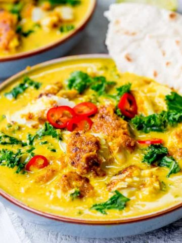 Square image of Thai fish yellow curry with kale.