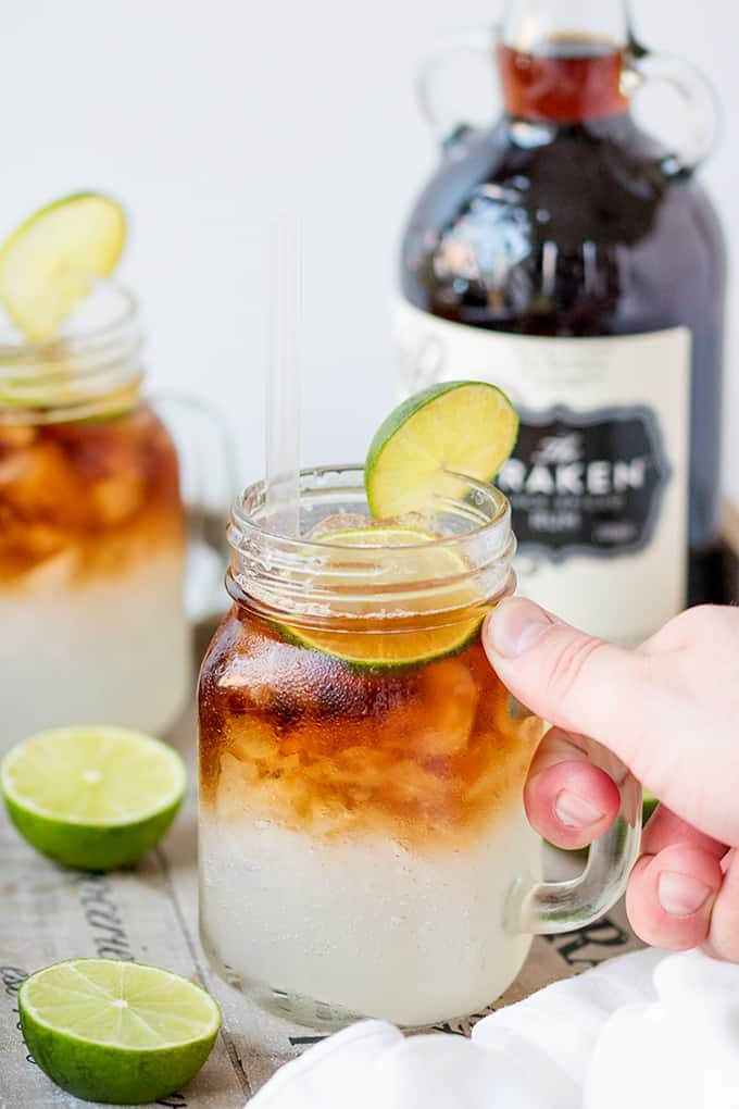 A mason jar with Dark 'N' Stormy cocktail in with a lime and a bottle of Kraken rum