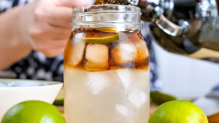 Pouring rum into a glass filled with ice and ginger beer