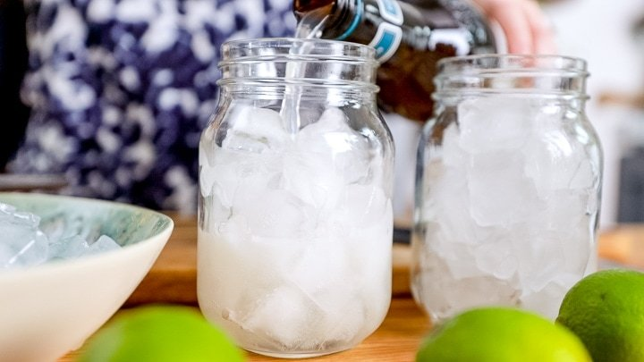 Pouring ginger beer into a glass full of ice