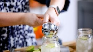 Squeezing lime into a mason jar for a cocktail