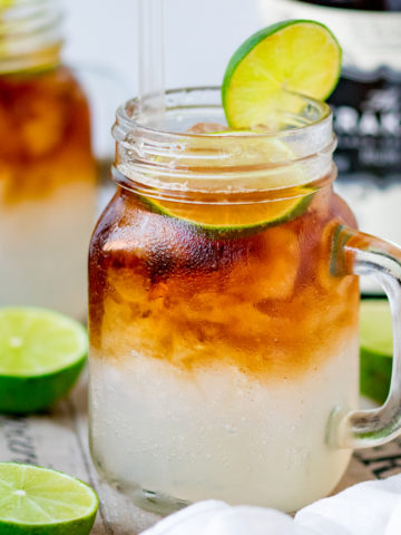 Mason jar glass filled with dark and stormy cocktail, topped with a slice of lime
