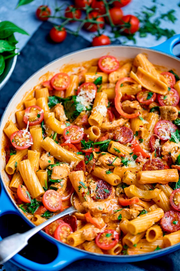 Cajun chicken pasta one pot in a blue pan with chopped cherry tomatoes