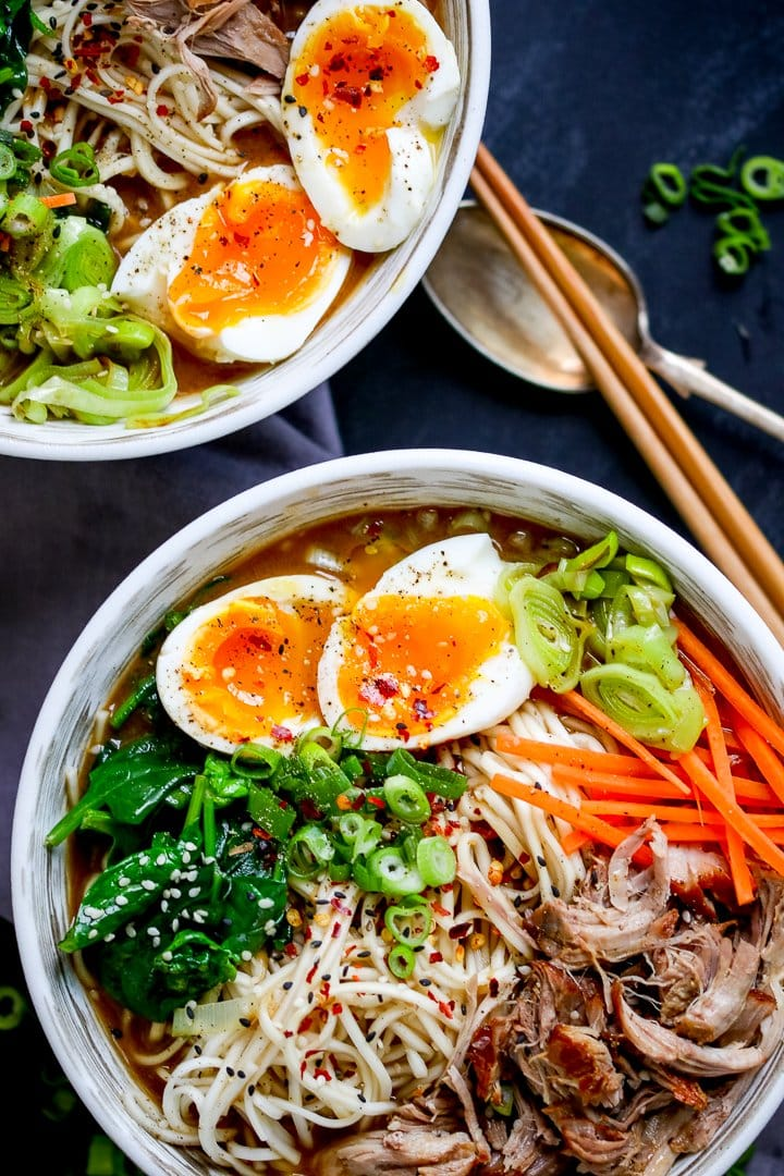 Overhead photo of 2 bowls full of pork ramen with pulled pork, noodles, spinach, runny eggs and broth on a blue background with a spoon and chopsticks