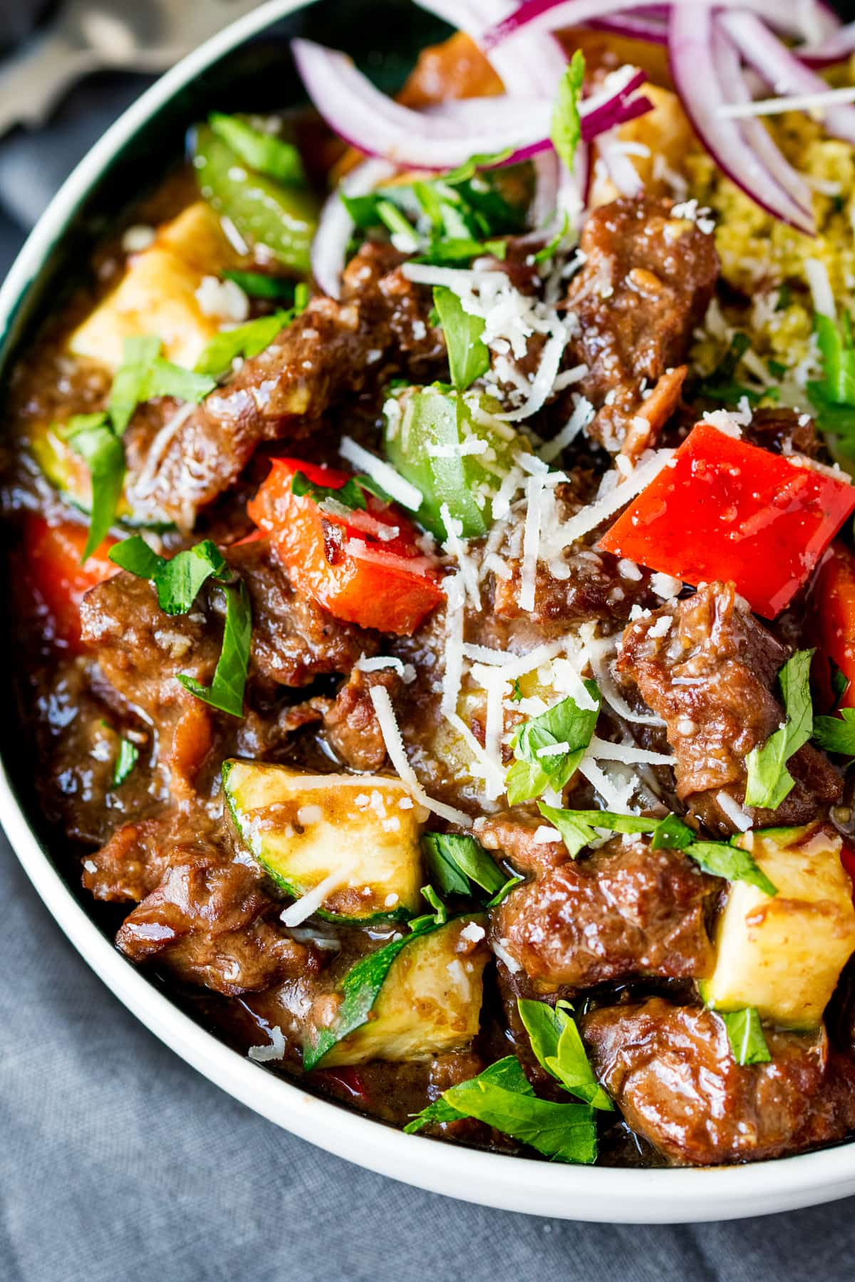 Close up overhead shot of summer beef casserole in a bowl with peppers, courgette and parmesan.