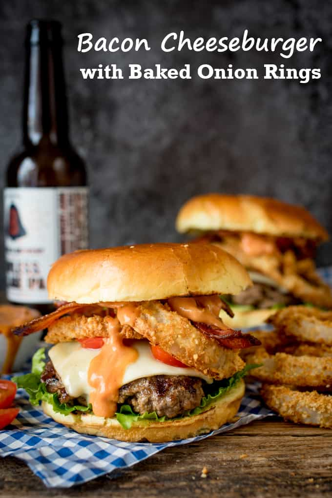 Bacon Cheeseburger with Baked Parmesan Onions Rings on a wooden board with a bottle of beer in the background