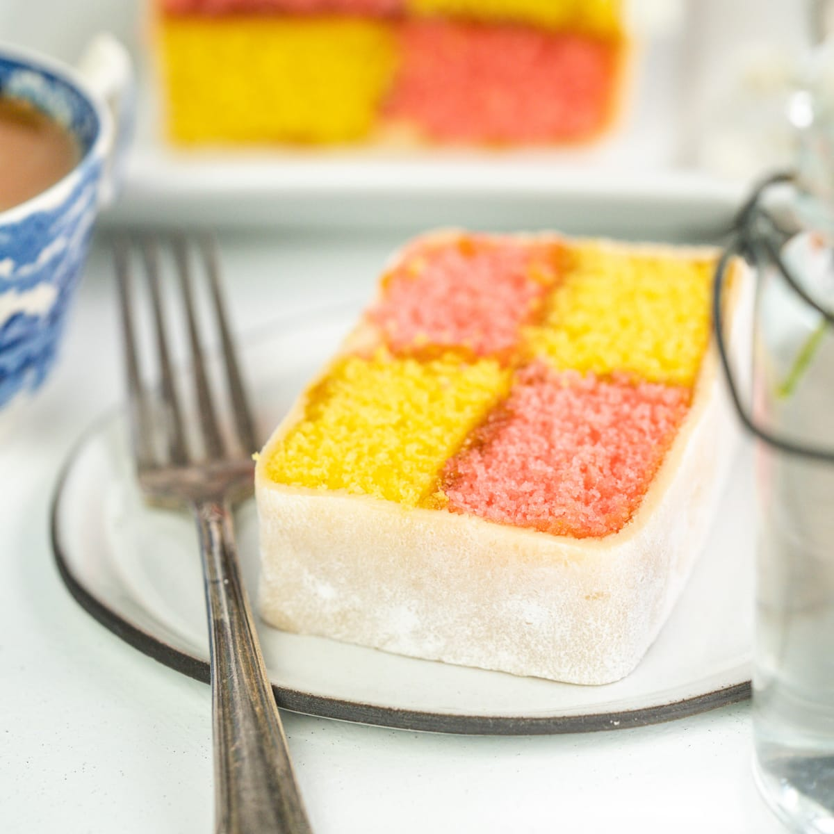 Battenberg cake slice on a plate with a fork on a light background.