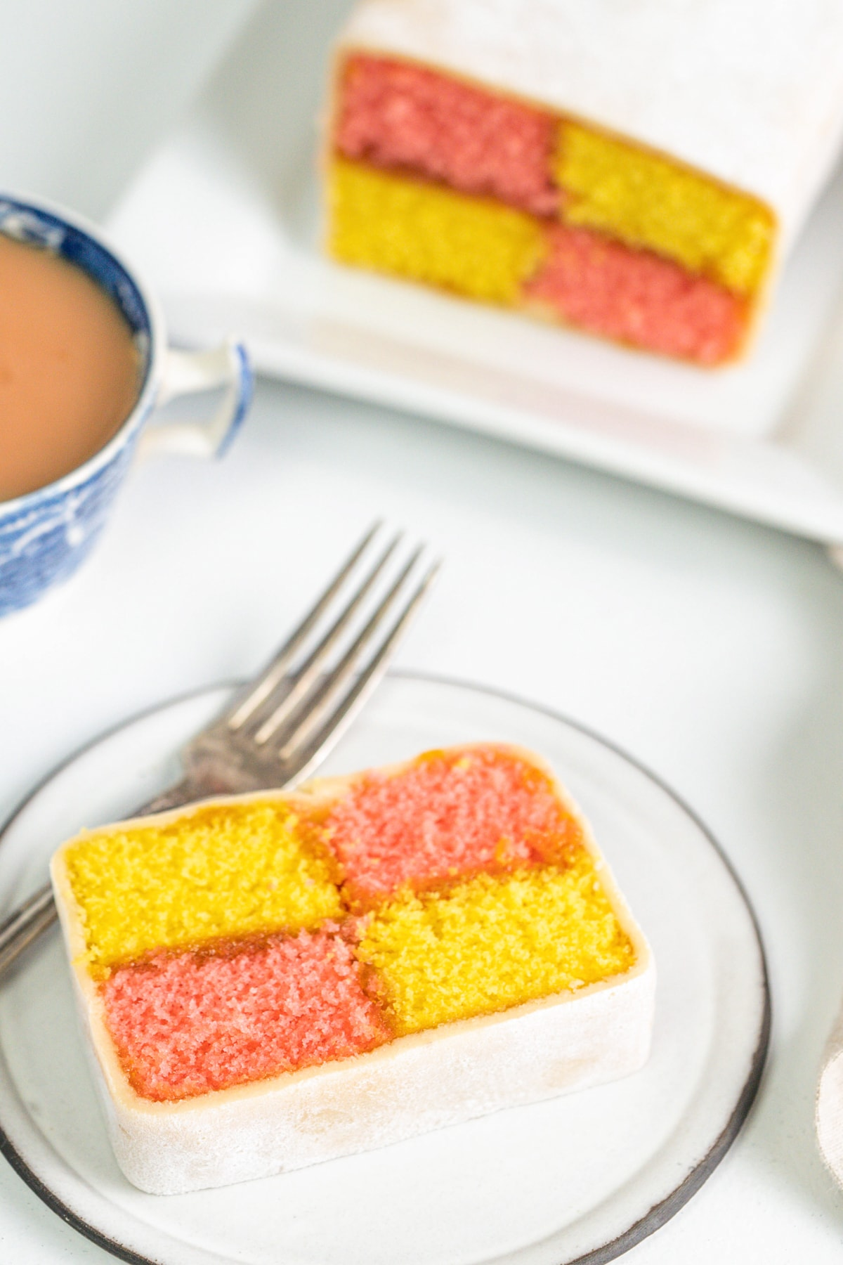 Slice of battenberg cake on a plate with a cup of tea and more battenberg in the background.