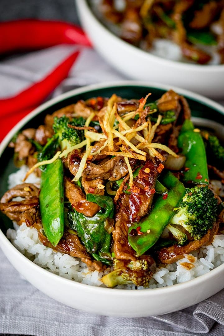 Ginger beef stir fry in a bowl with broccoli and rice