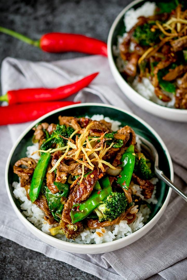 ginger beef with broccoli in a white bowl, topped with fried ginger