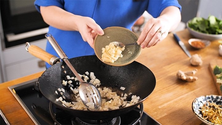 Garlic and ginger being added to a wok that has fried onions in it.