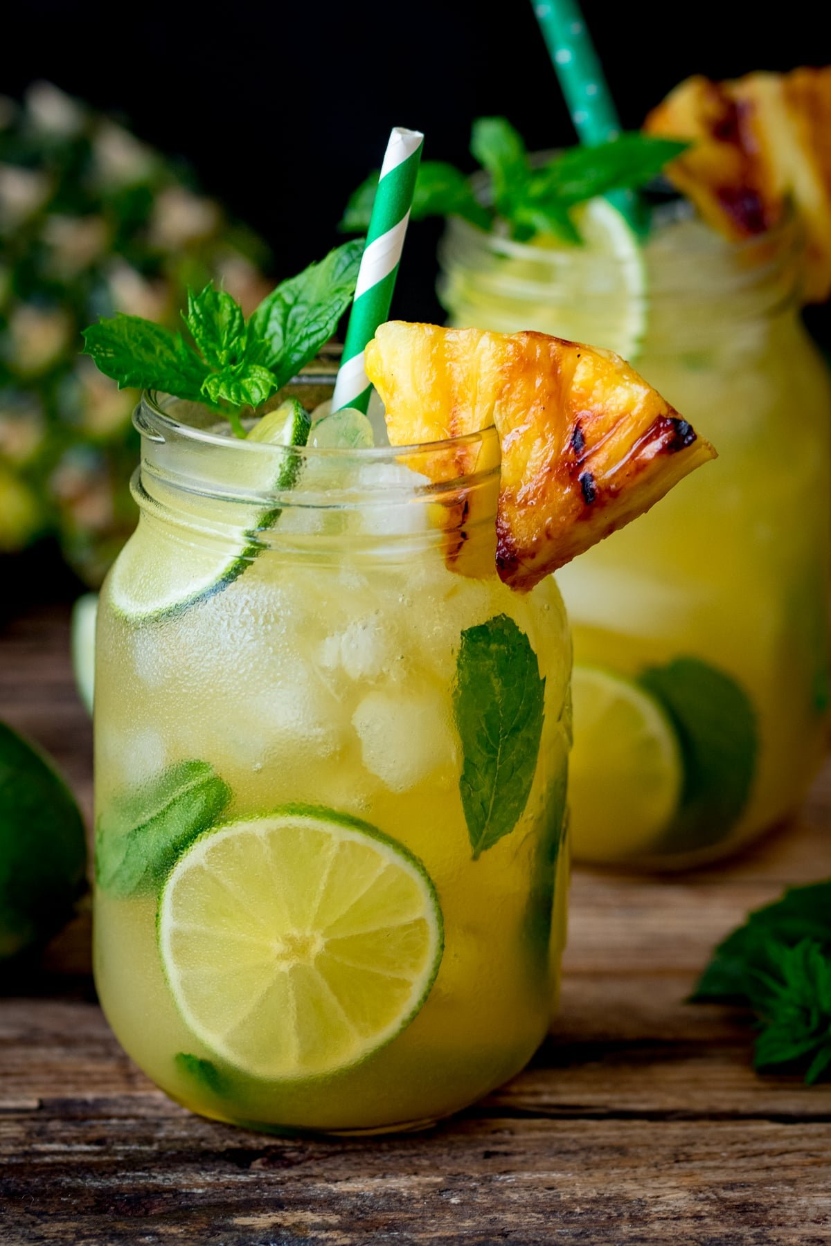 2 Pineapple Ginger Mojitos in mason jars decorated with wedges of caramelized pineapple.
