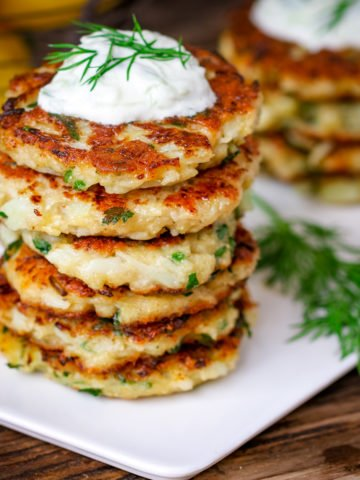 Square image of a stack of cauliflower fritters topped with tzatziki on a white plate on a wooden board.