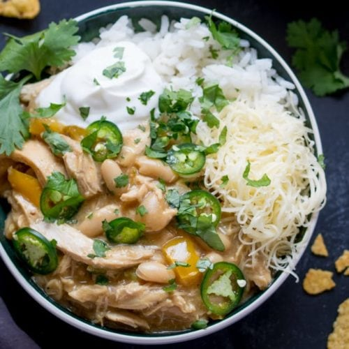White chilli chicken in a bowl with rice, cheese, jalapenos and spring onions