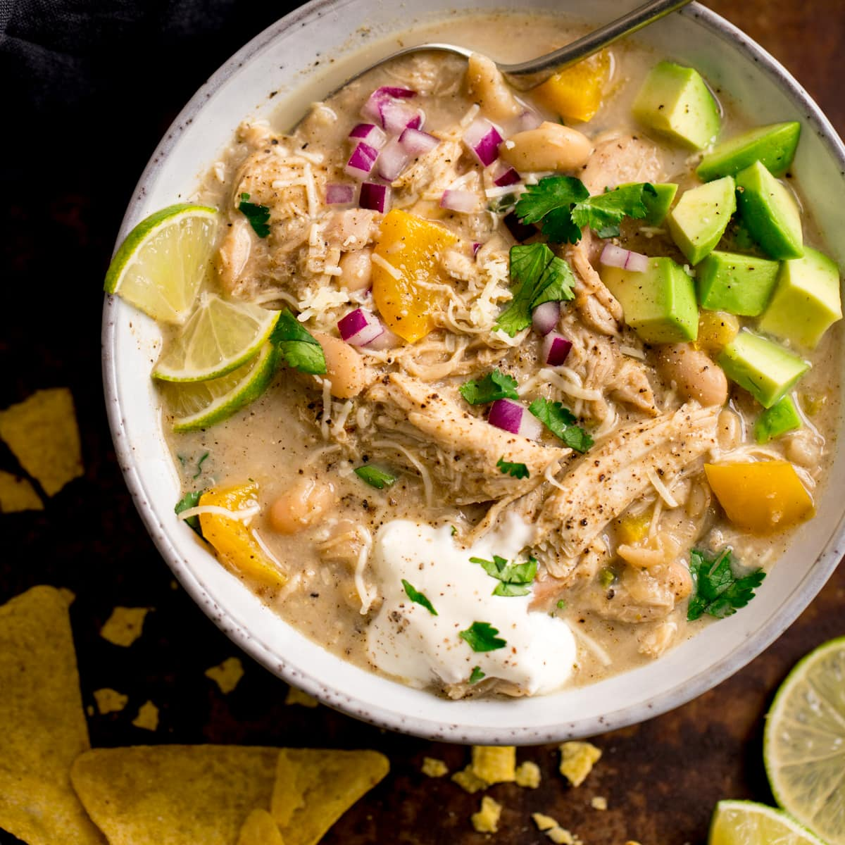 white chilli chicken con carne in a white bowl topped with lime wedges, avocado chunks and red onion. Tortilla crisps next to the bowl.