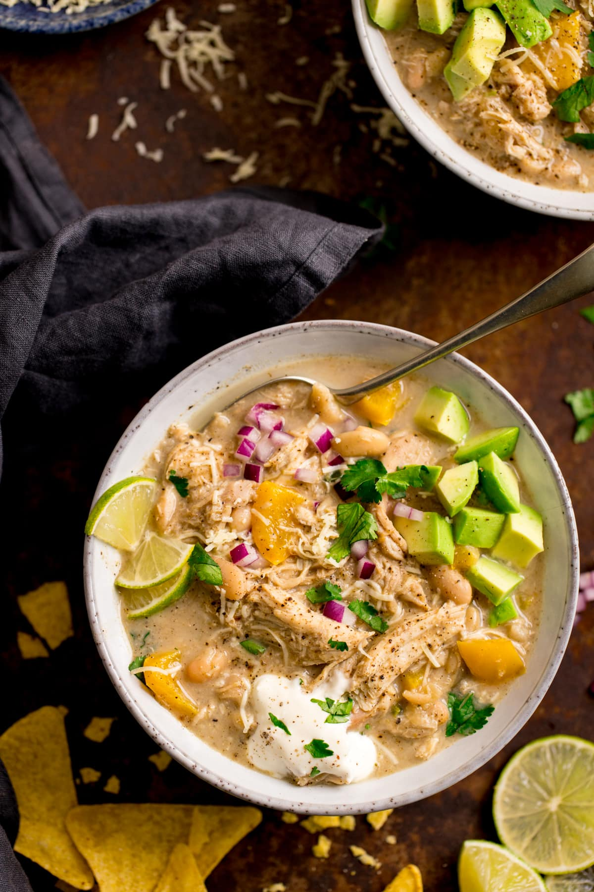 White bowl filled with white chilli chicken con carne on a dark background. Second bowl just in shot. Ingredients and a grey napkin are scattered around the bowl.