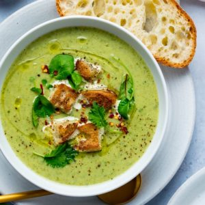 Broccoli Cheese Soup croutons and baby leaves in a white bowl