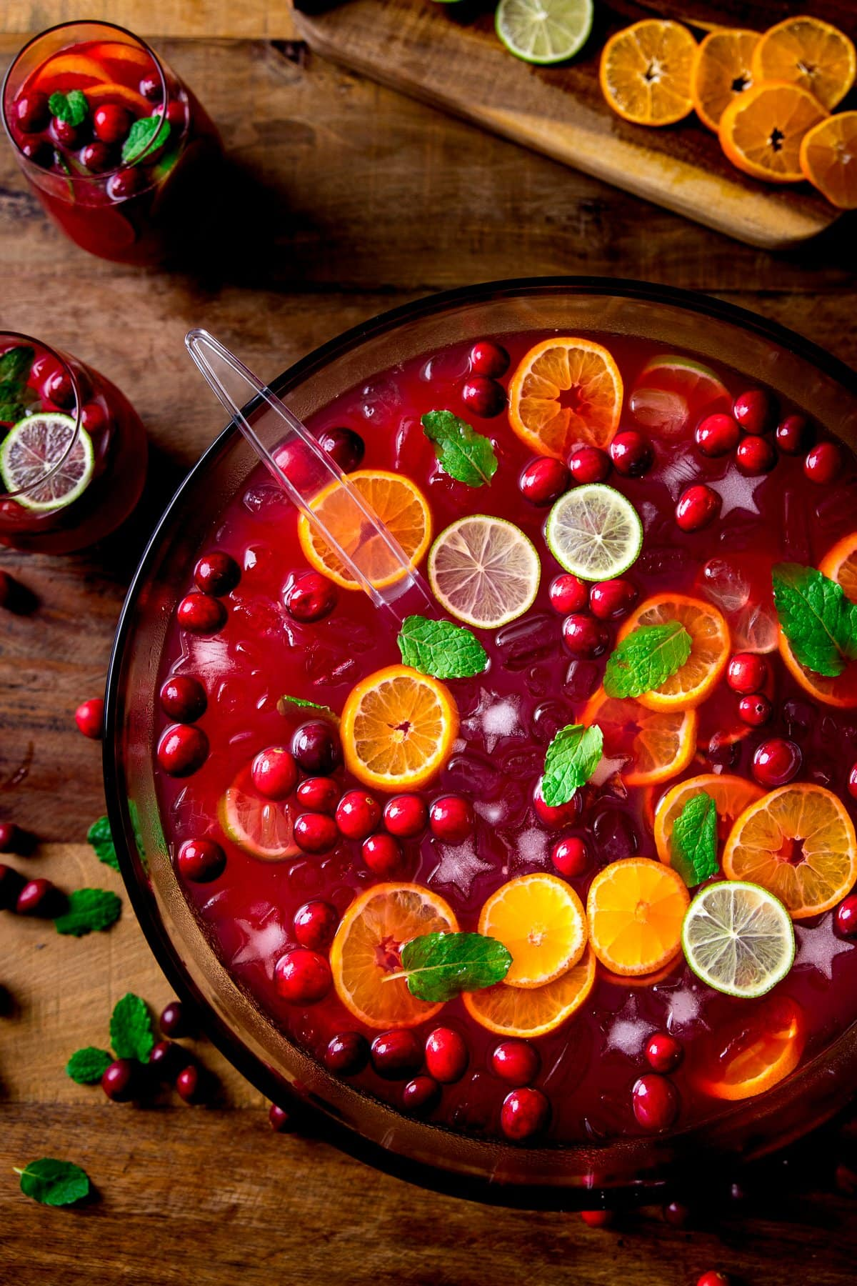 Festive Punch in a bowl on a wooden table. Punch is topped with slices of citrus fruits and cranberries