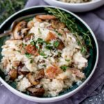 Turkey, pancetta and mushroom risotto in a bowl with fresh thyme on top