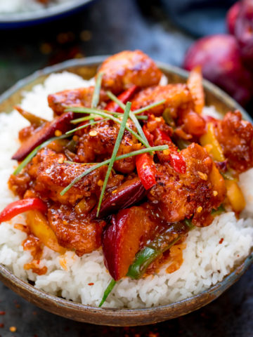 Chinese plum chicken stir fry and rice in a bowl. Whole plums and blue napkin next to bowl.
