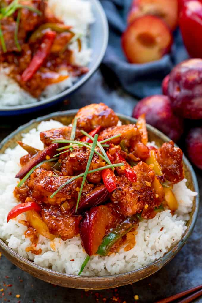 Chinese plum chicken stir fry and rice in a bowl. Further bowl at the top of the frame. Whole and halved plums and blue napkin next to bowls.