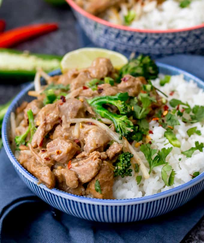 Close up photo of Thai style peanut pork in a blue bowl with rice