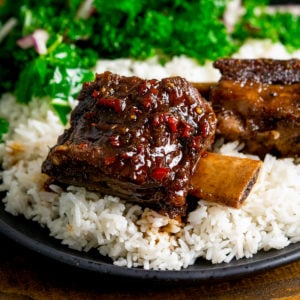 Sticky chilli-glazed short ribs on a bed of rice on a dark plate with kale in the background.