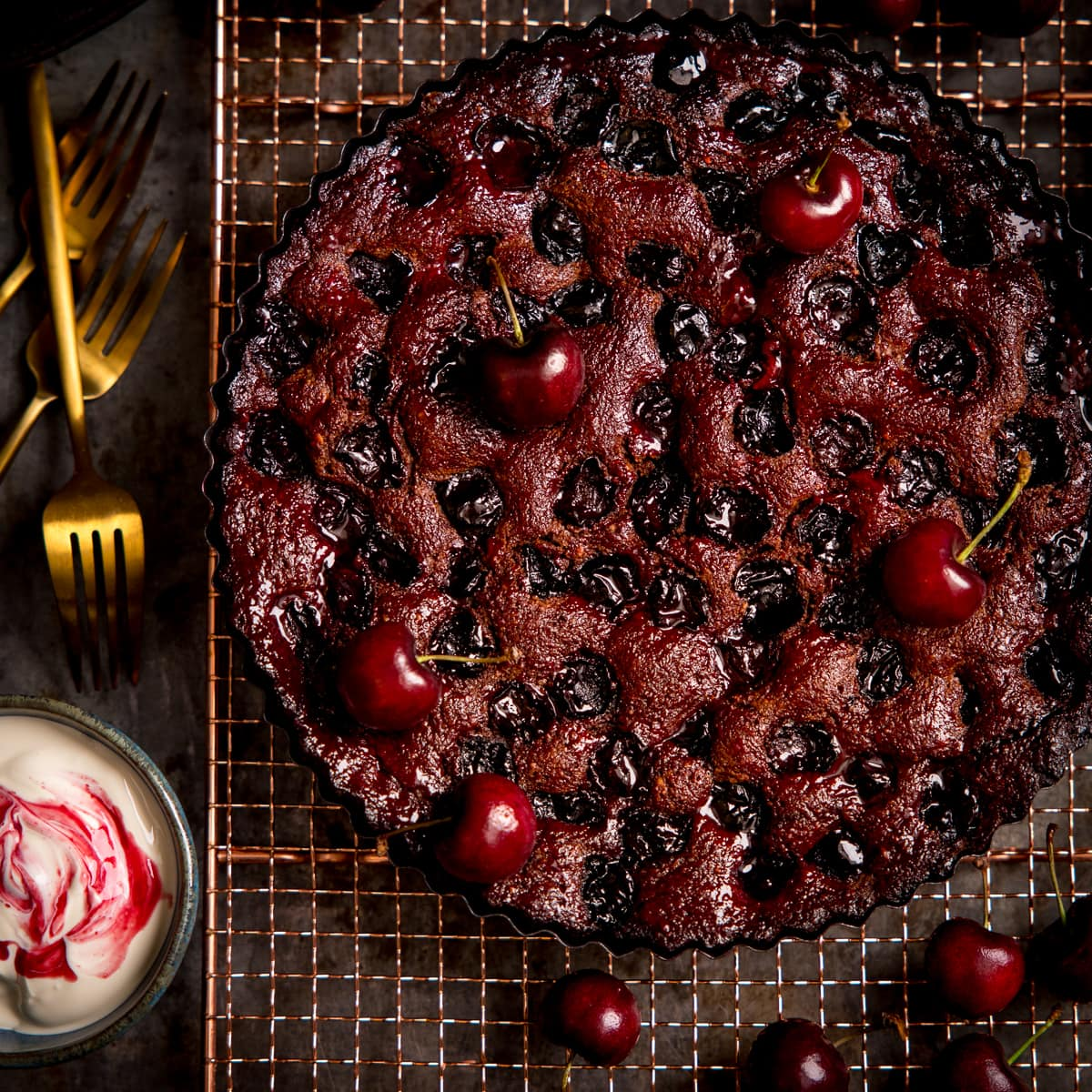Chocolate Cherry Cake on a wire rack with cherries scattered around.