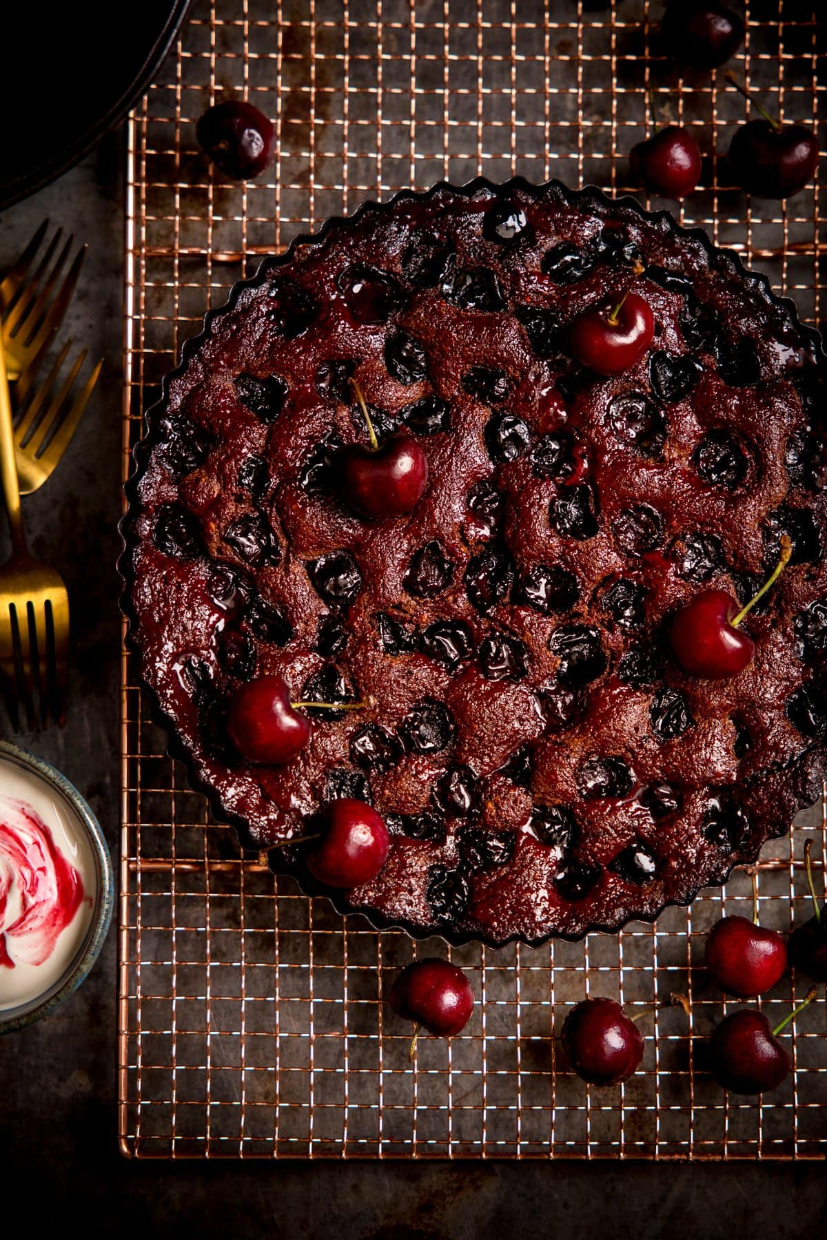 Overhead image of Chocolate Cherry Cake on a wire rack with cherries scattered around.