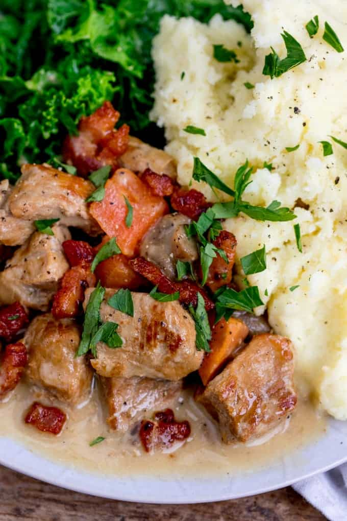 Closeup overhead photo of Creamy Slow Cooked Pork Casserole with mash potato and kale