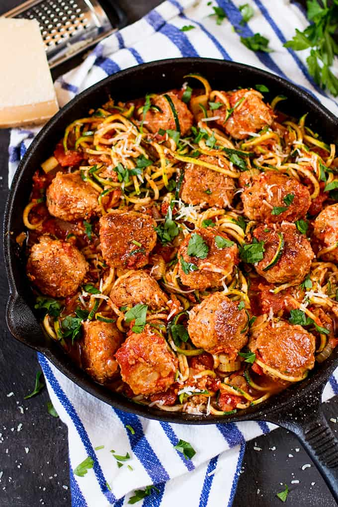 Overhead picture of Turkey Meatballs With Courgetti in a skillet on a blue and white cloth