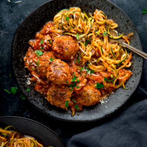 Square image of Turkey meatballs and courgetti on a dark plate