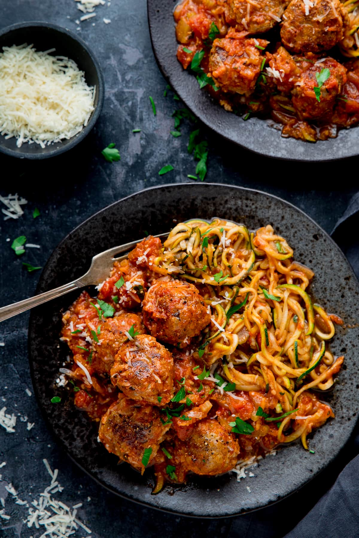 Turkey meatballs and courgetti on a black plate against a dark background